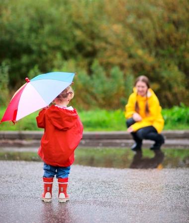 botas de lluvia: Madre e hija al aire libre en el lluvioso día de otoño