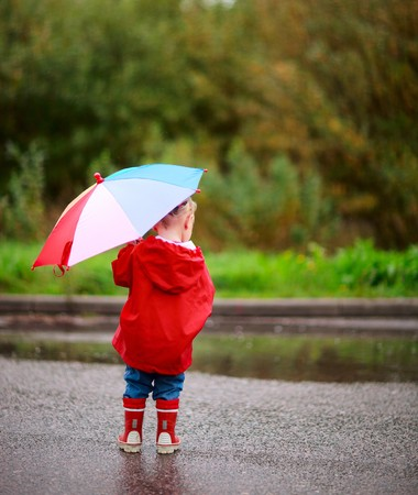 Back view of toddler girl with colorful umbrella outdoors at rainy day photo