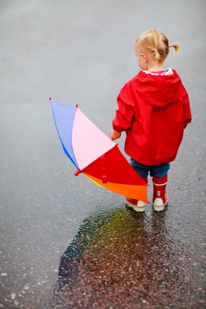 rainy season: Back view of toddler girl outdoors at rainy day