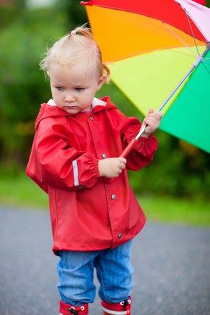 Portrait of cute toddler girl with colorful umbrella photo