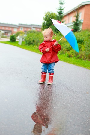Adorable toddler girl with colorful umbrella outdoors at rainy day Stock Photo - 7819899