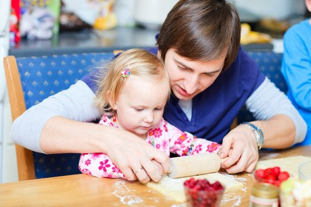 Adorable toddler girl at kitchen baking pie together with her father  photo