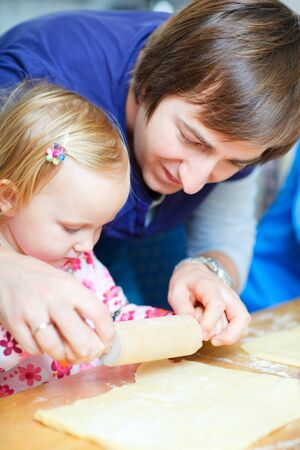Young father baking together with his little daughter photo
