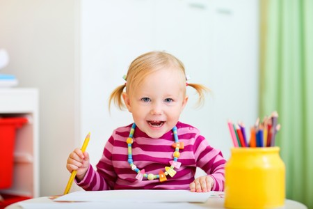 Cheerful toddler girl drawing with pencils. Stock Photo - 7819948