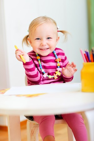 Portrait of playful toddler girl drawing with pencils photo