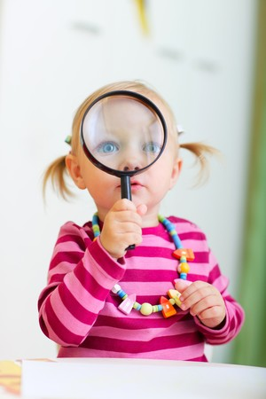 Portrait of adorable toddler girl looking through magnifier Stock Photo