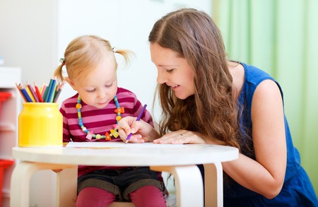 kindergarden: Young mother and her little daughter drawing together Stock Photo
