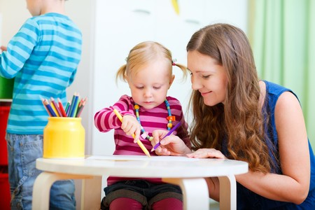 Young mother and her daughter drawing together. Also perfect for kindergarten/daycare context. Stock Photo - 7819991