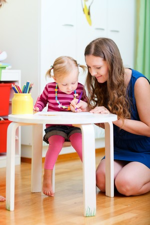 Vertical photo of mother and daughter drawing together photo