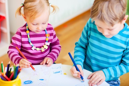 kindergarden: Brother and little sister drawing with coloring pencils in their room Stock Photo