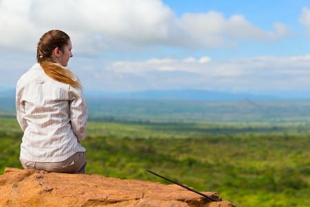 Achteraanzicht van jonge vrouw zit op de rand van de klif en uitzicht van de savanne