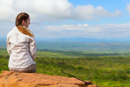 expeditions: Back view of young woman sitting at cliff edge and enjoying savanna views Stock Photo
