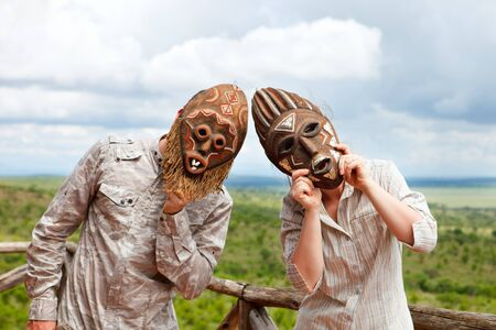 Couple in African masks standing at balcony with view to savanna photo