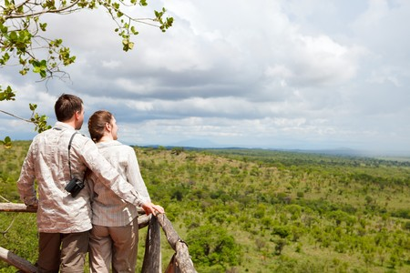 arial views: Couple on safari vacation looking to savanna from balcony Stock Photo