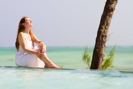 Beautiful woman relaxing by swimming pool at tropical destination photo