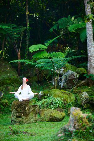 Young beautiful woman meditating outdoors at tranquil environment photo