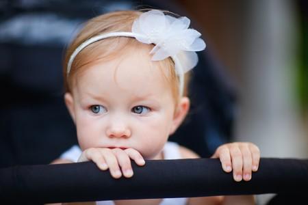 baby stroller: Portrait of adorable toddler girl sitting in stroller