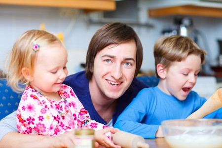 Portrait of young father with his two kids at kitchen photo