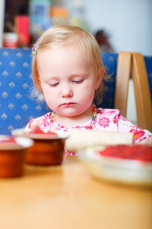 Adorable toddler girl helping at kitchen with baking photo