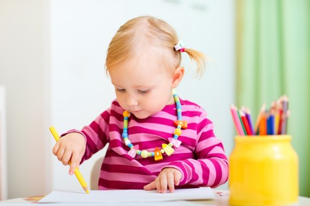 Cute little girl coloring with pencils at home photo