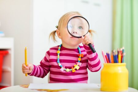 Funny photo of adorable toddler girl looking through magnifier Stock Photo - 7941688