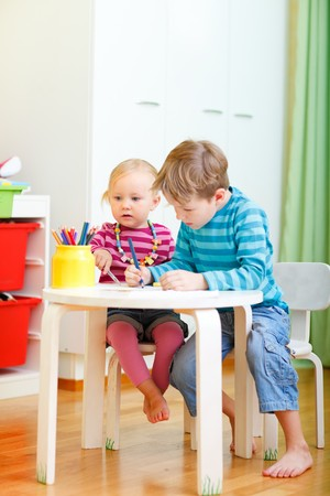Vertical photo of two small kids drawing together at their room photo