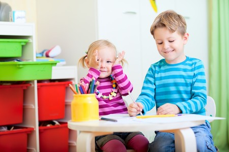 Happy brother and sister sitting together at table and drawing with pencils photo