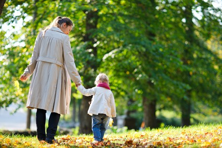 Back view of mother and daughter walking in beautiful autumn park photo