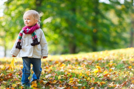 Adorable toddler girl with yellow leaf in autumn park