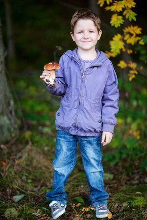 Full body portrait of cute boy with wild mushroom at forest photo