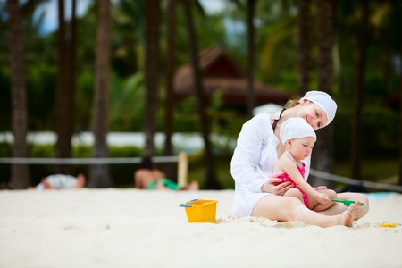 Mother and her little daughter playing with toys at beach photo