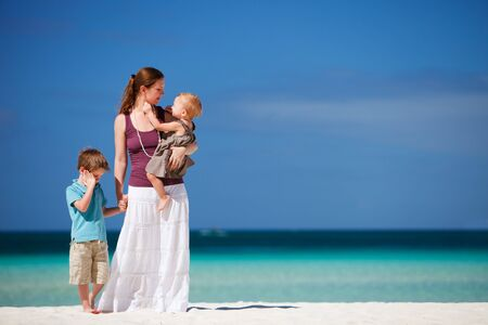Young mother with her son and daughter on tropical beach vacation photo