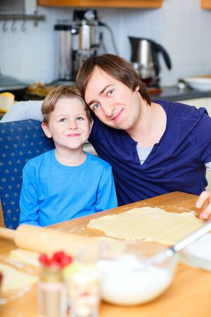 Father and his son baking together a pie photo