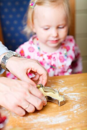 Closeup of father helping his little daughter with baking cookies Stock Photo - 7941744