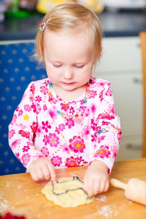 Cute little girl helping at kitchen with baking cookies photo