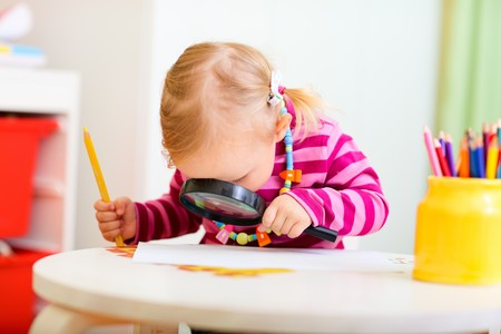 magnifying: Funny photo of adorable toddler girl looking through magnifier
