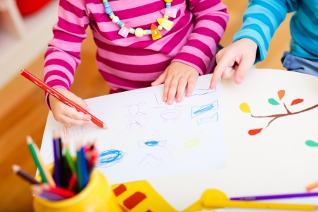 kindergarden: Closeup of two kids drawing with coloring pencils