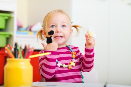 Adorable toddler girl playing with finger puppets photo