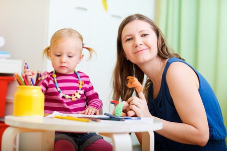 Young mother and her adorable little daughter playing with finger puppets photo