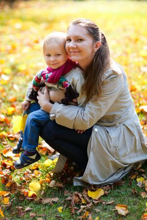 Portrait of young mother and her little daughter outdoors on sunny autumn day photo