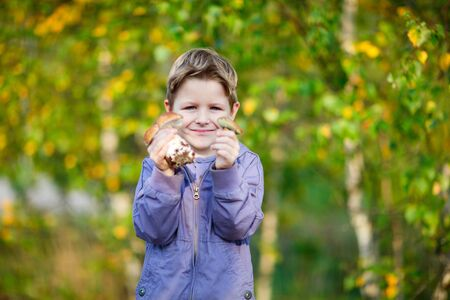 Portrait of happy kid showing two wild mushrooms photo