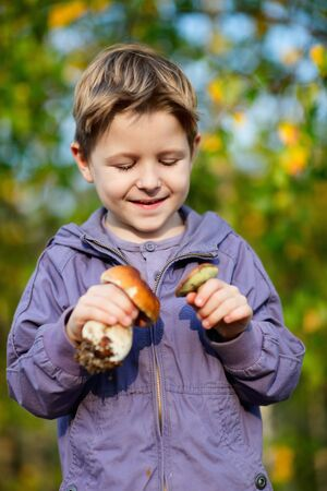 Portrait of happy boy with two wild mushrooms photo