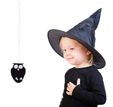 Halloween dressed toddler girl in black  little witch costume looking to small owl photo