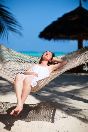Young beautiful woman relaxing in hammock at tropical beach photo