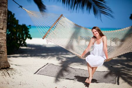 Young beautiful woman relaxing in hammock at tropical beach photo