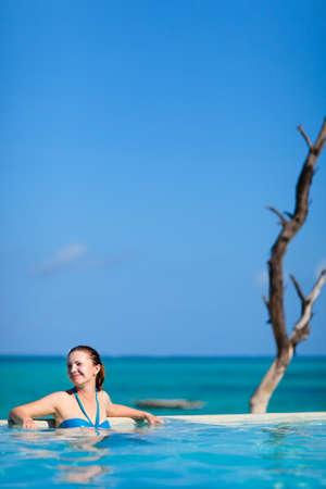 Beautiful young woman relaxing in swimming pool photo