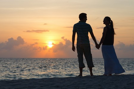 Silhouettes of romantic couple on tropical beach at sunset photo