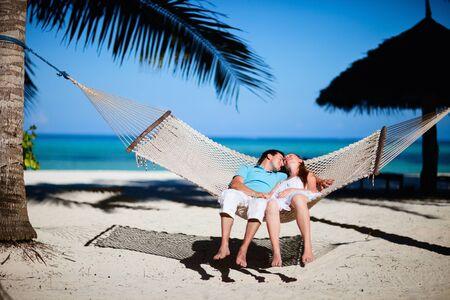 hamaca: Joven pareja romántico relajaba en hamaca en playa tropical