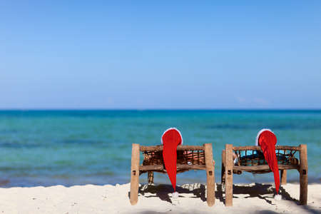 Couple in red Santa hats at tropical beach relaxing on sun beds photo
