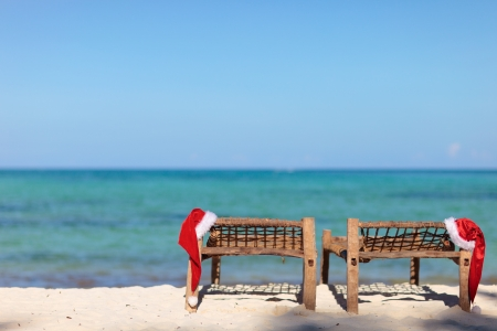Two santa hats on sunbeds at tropical beach photo